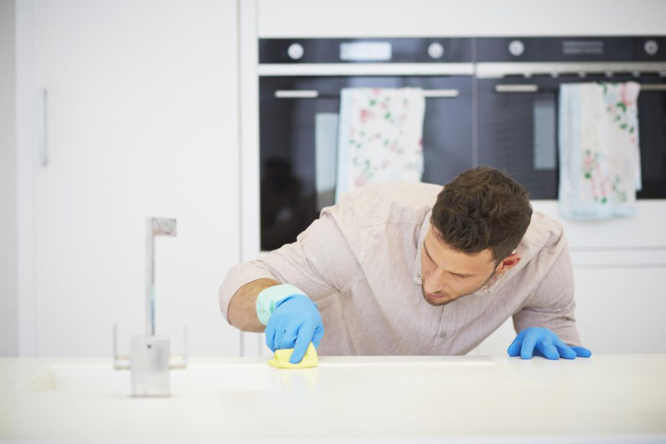 Man carefully scrubbing kitchen