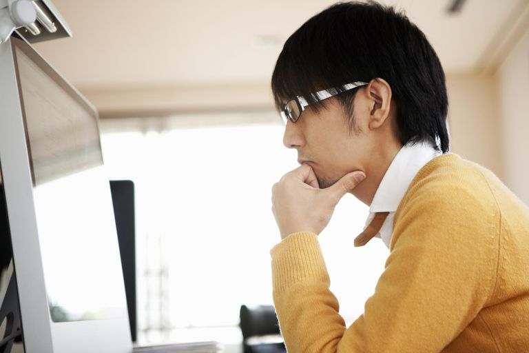 A web designer resting his chin in his hand and watching a desktop computer.