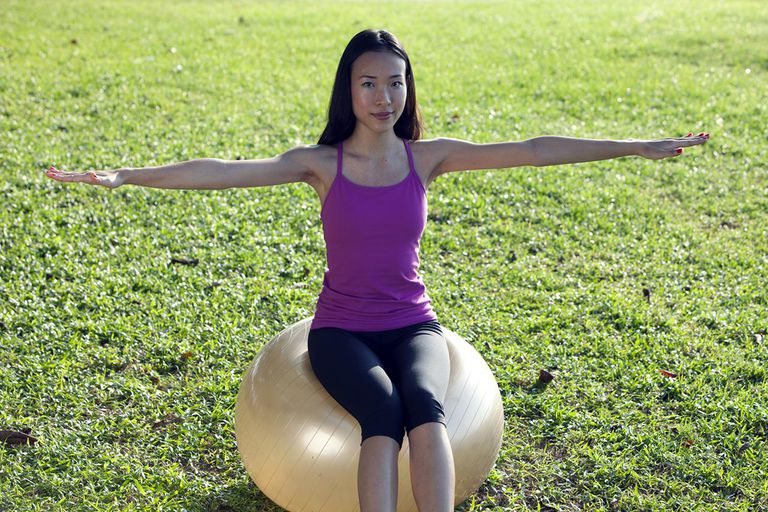 Asian woman with fitness ball exercising with arms outstretched