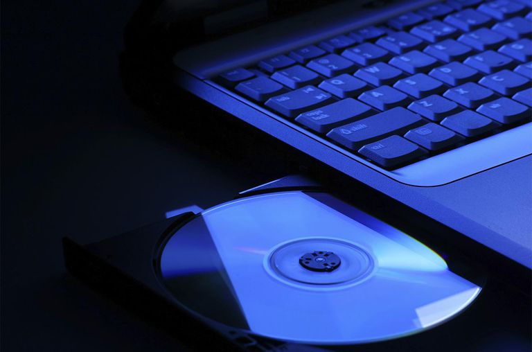 Laptop with open dvd drive in blue light