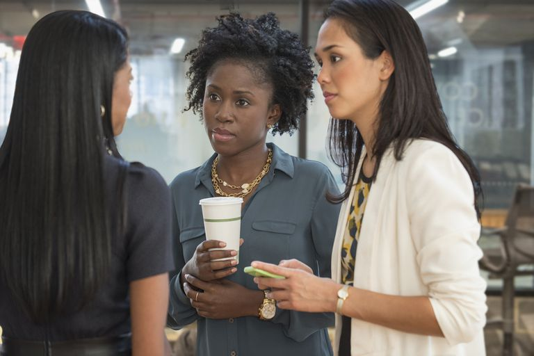 Three multicultural women, including an HR manager, talk about an organizational issue.