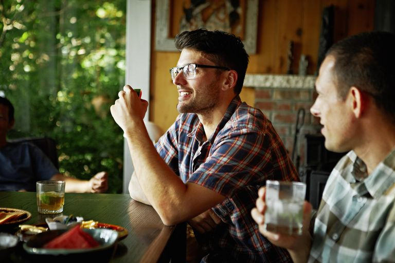 Smiling friends eating and drinking in cabin