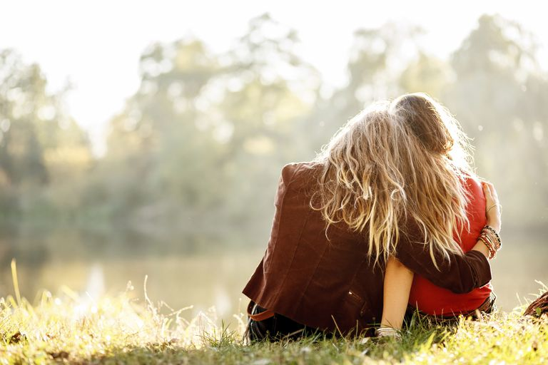 Two young girls in a field looking away