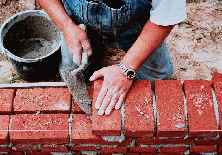 Man in overalls laying bricks