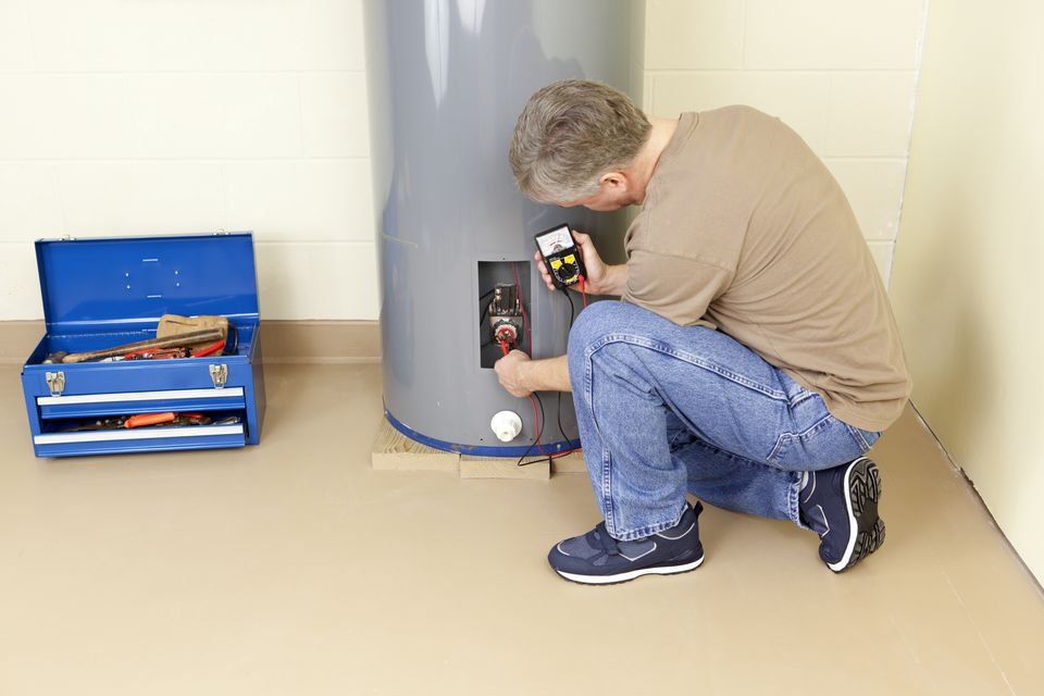 A plumber working in a water heater