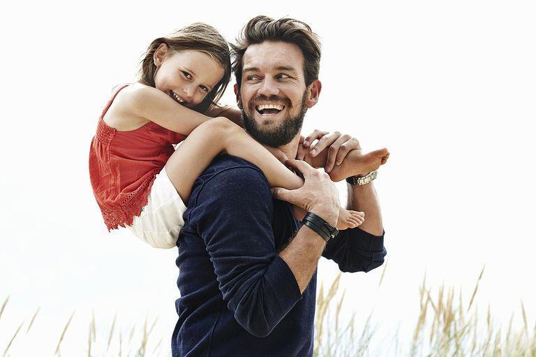 Dad giving his daughter a piggyback ride