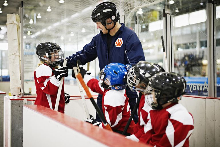 kids with coach at ice hockey rink