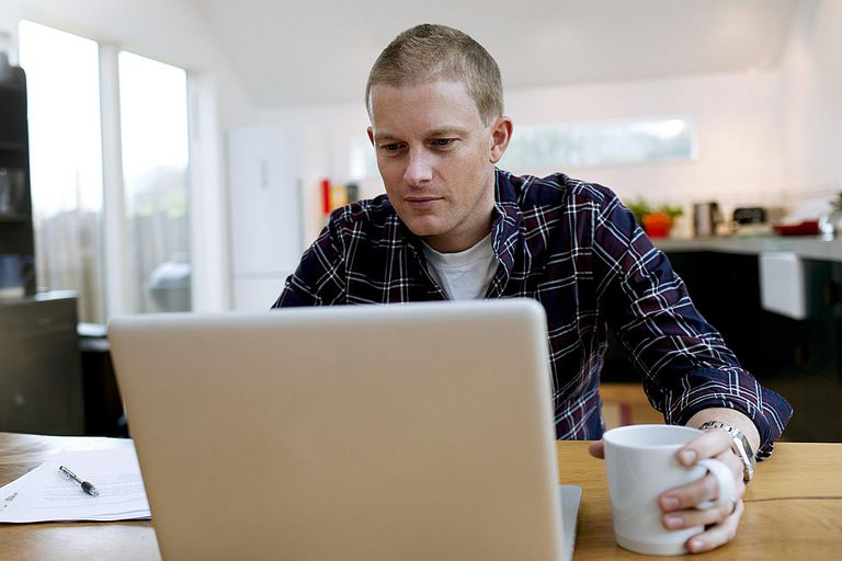 A man works on a laptop computer.