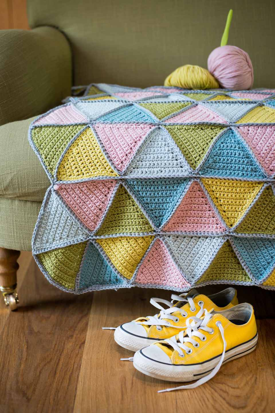 Yellow Sneakers Under Couch with Yarn and Knitted Woolen Mat