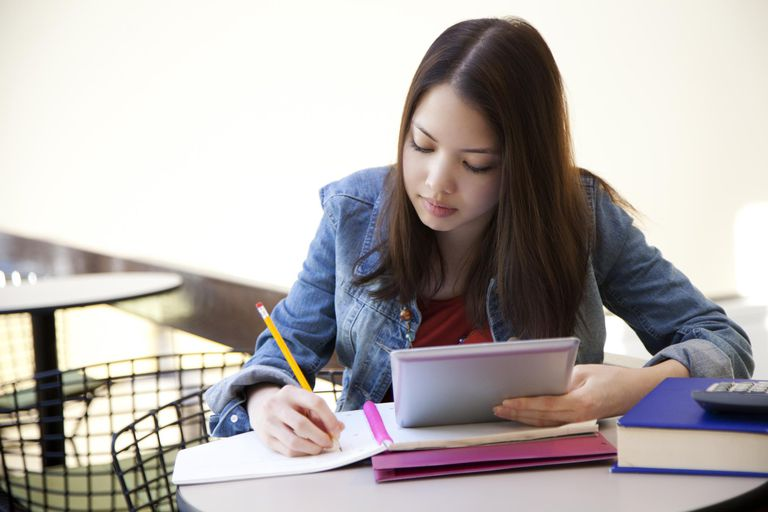 Ethnic student studying with digital tablet