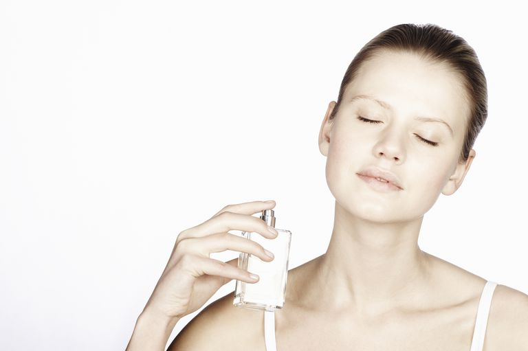 Woman spraying perfume onto her neck
