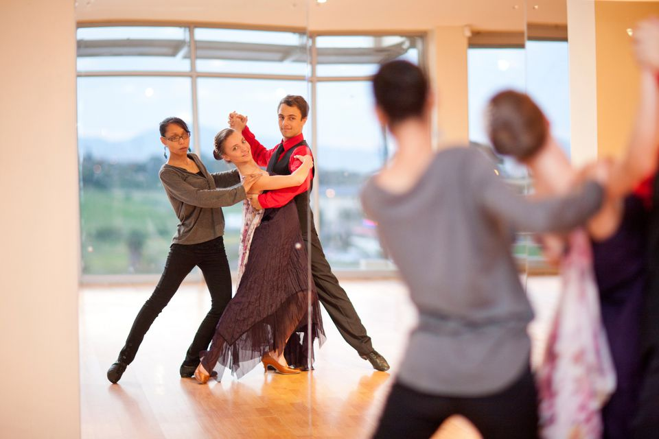 Dance teacher and ballroom dancers looking in mirror