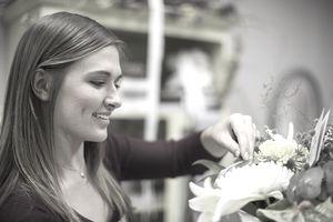 Smiling florist arranging bunch of flowers