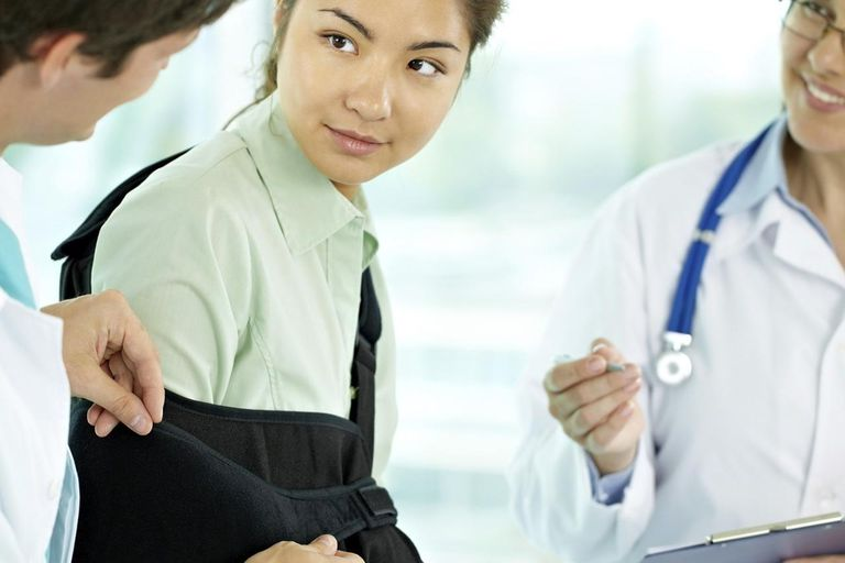Doctor fixing hand of a young patient in an arm sling