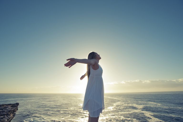 woman with arms thrown back standing over water