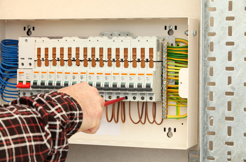 Electrician working at a fuse box