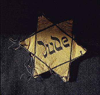 A yellow Star of David badge bearing the German word Jude.