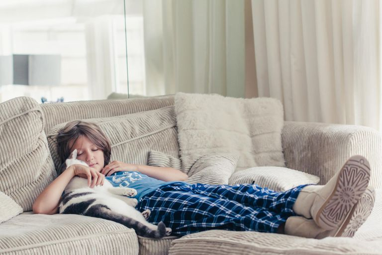 Boy lying on a couch in his pj's cuddling his cat