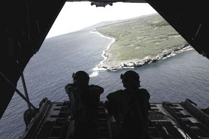 Loadmasters look out over Tumon Bay from a C-130 Hercules.