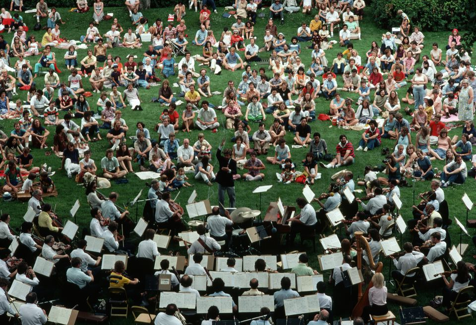 Musicians play an outdoor concert for an audience at the University of Minnesota. | Location: University of Minnesota, Minneapolis, USA.