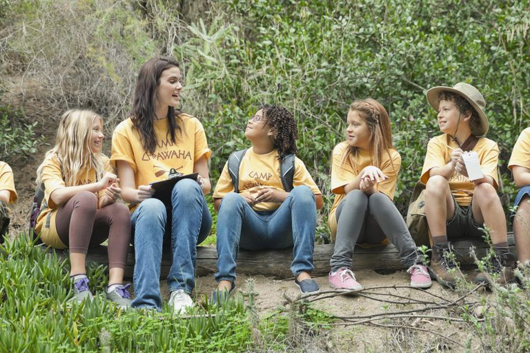 Camp counsellor and children sitting on log in forest.