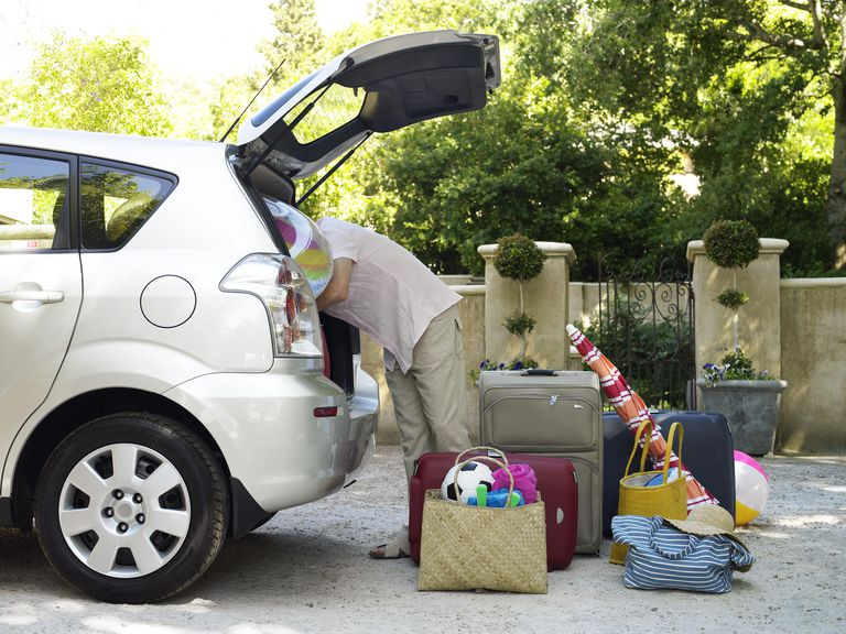 Man looking into boot with suitcases and beach equipment