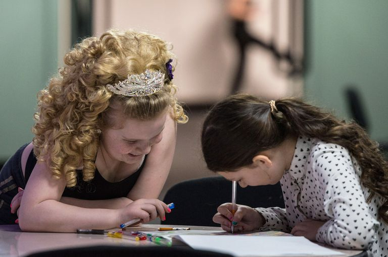 two young girls working in an activity book