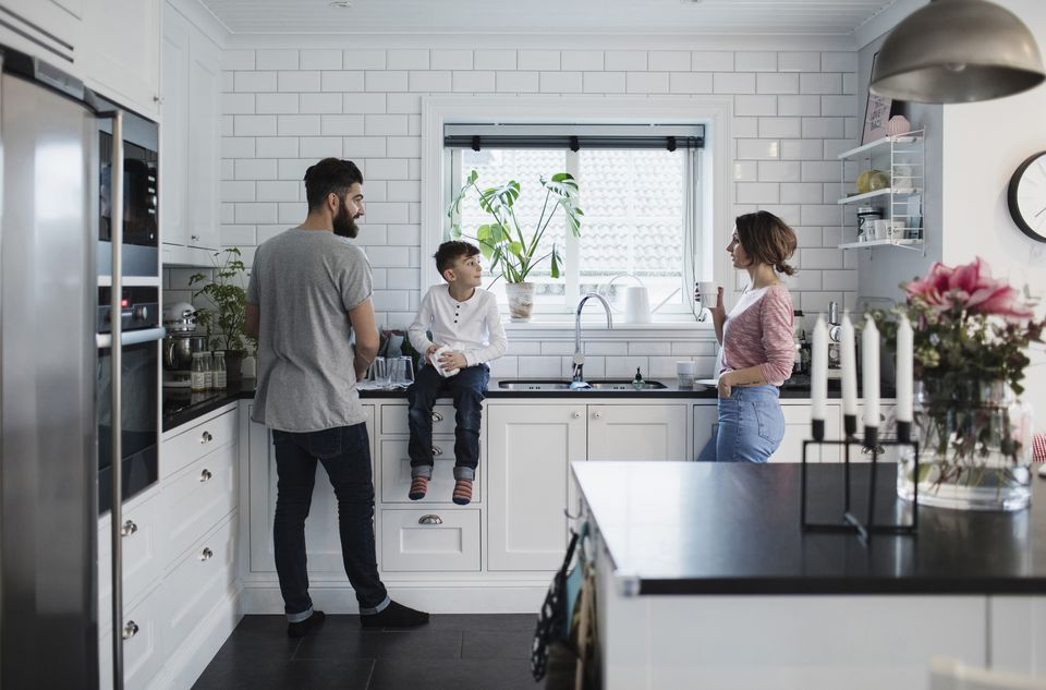 Father and mother with son in kitchen at home