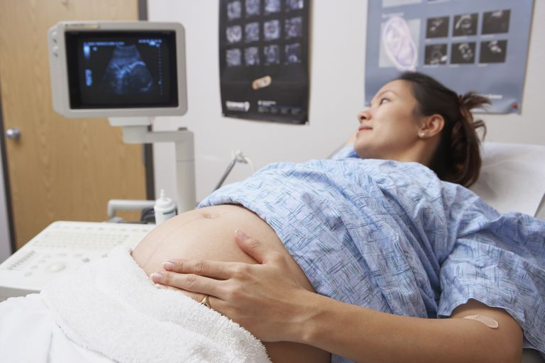 Pregnant Asian woman looking at ultrasound machine in hospital