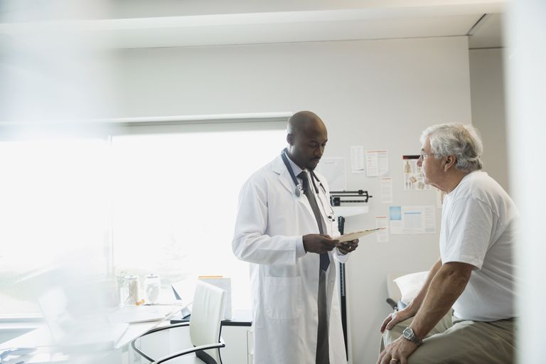 doctor discussing medical chart with male patient