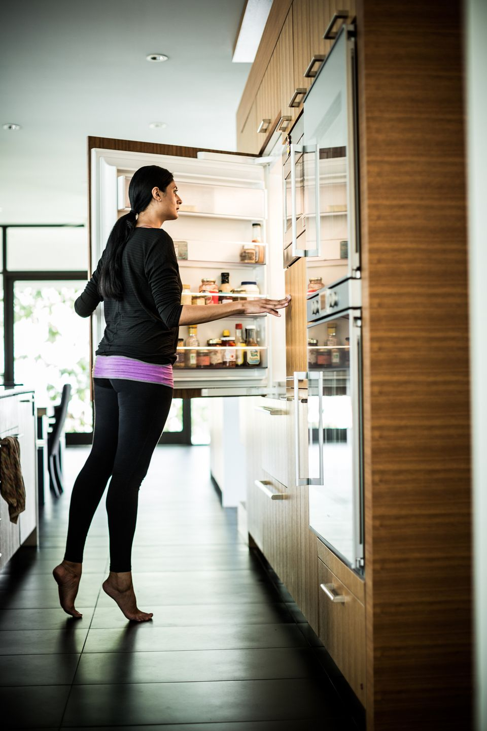 A woman opening a counter-depth fridge