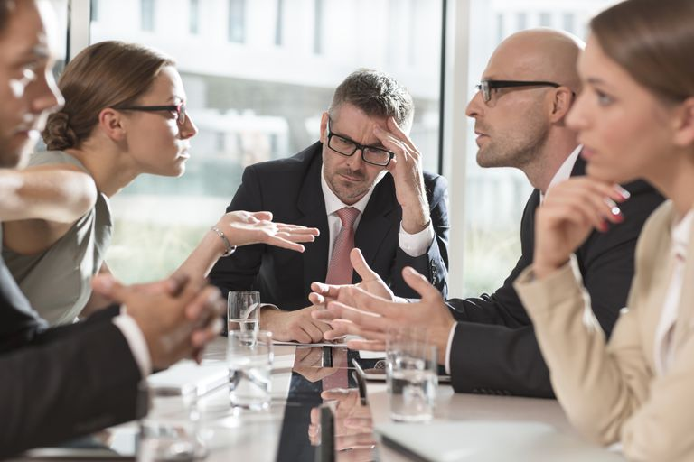 Two women and three men arguing and negative at a meeting