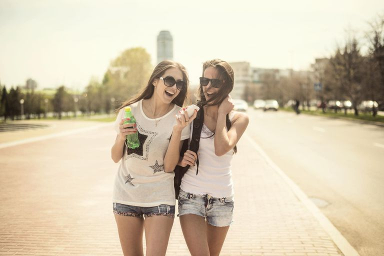 Two Teen Girls Laughing and Texting on Smartphone