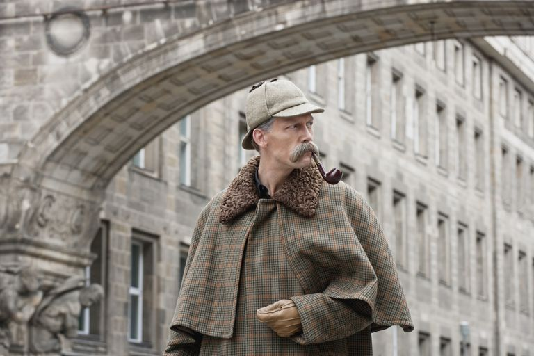 A man dressed up as Sherlock Holmes standing under a building arch looking away