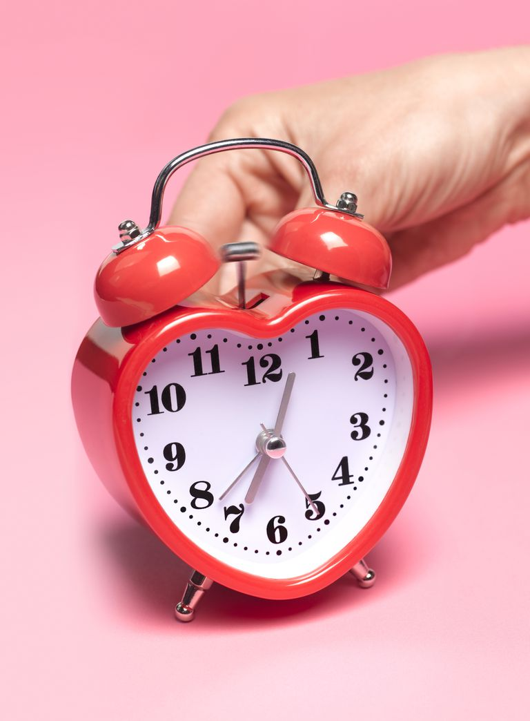 Woman adjusting back of red heart shaped clock, metaphor for biological fertility clock