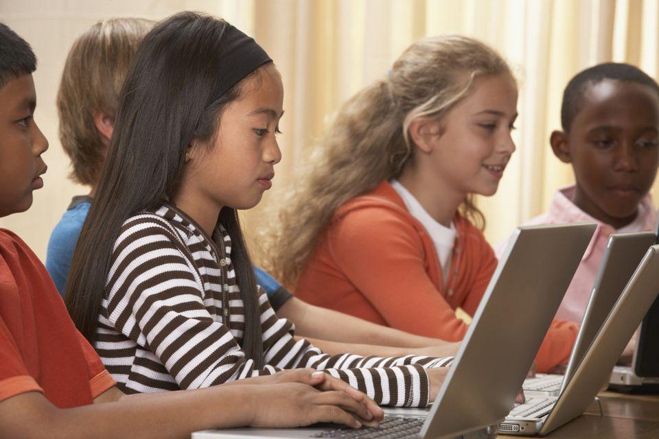 Multi-ethnic children typing on laptops