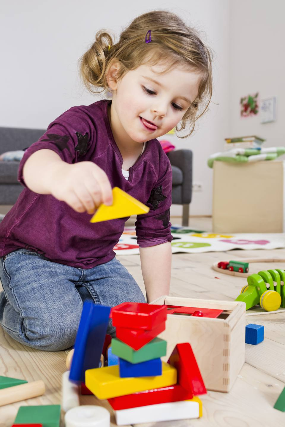 Toddler girl makes a tower with blocks