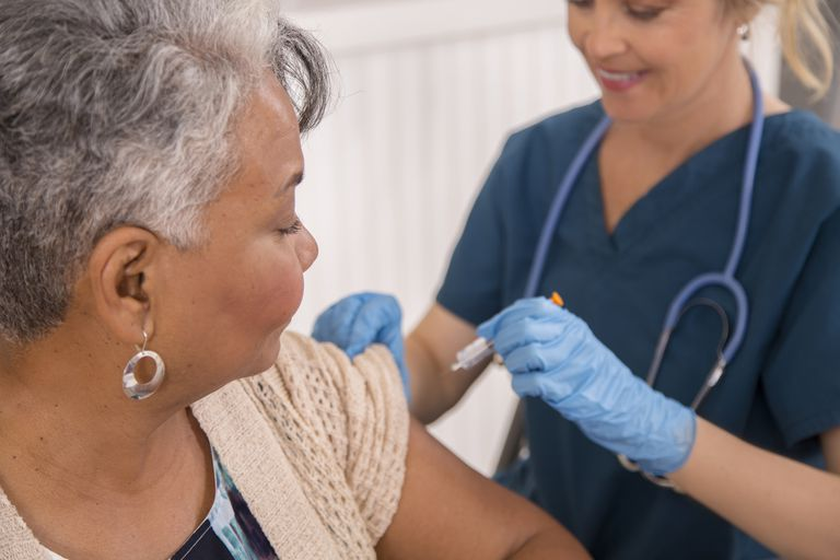 Nurse giving immunomodulator injection to patient