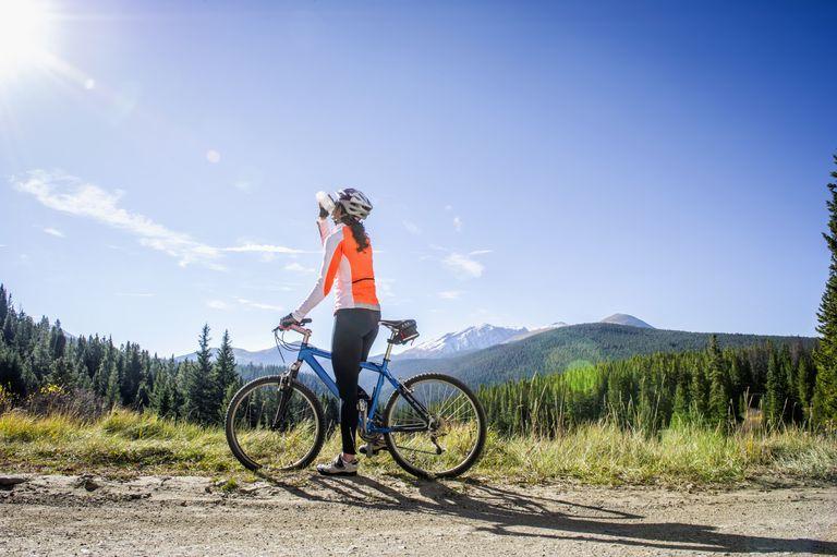 Woman riding bike through rural landscape