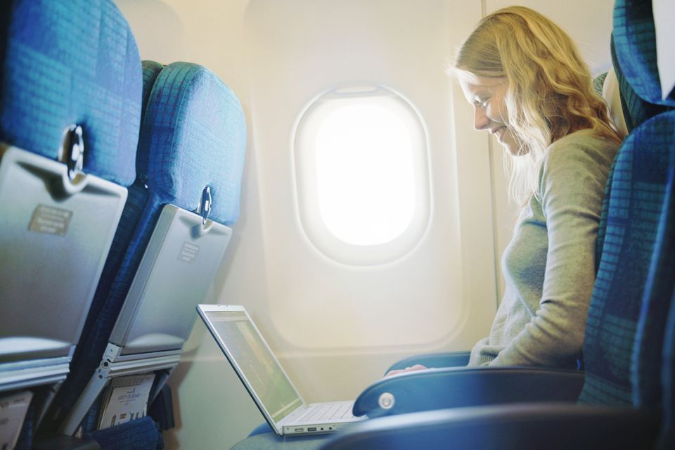 Woman using a laptop in an airplane