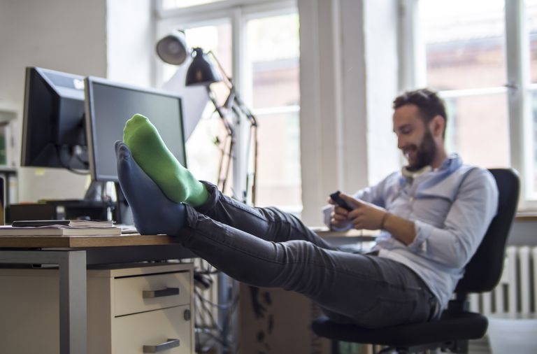 A young professional with his feet up using his mobile phone.