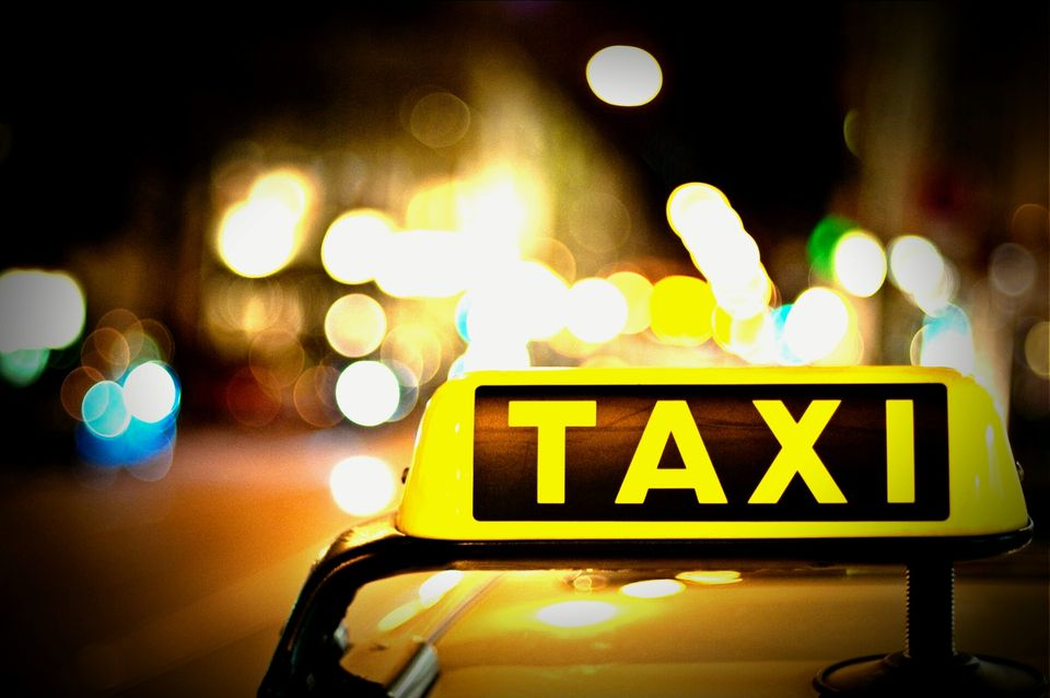 Close-Up Of Illuminated Taxi Sign On Taxi In City