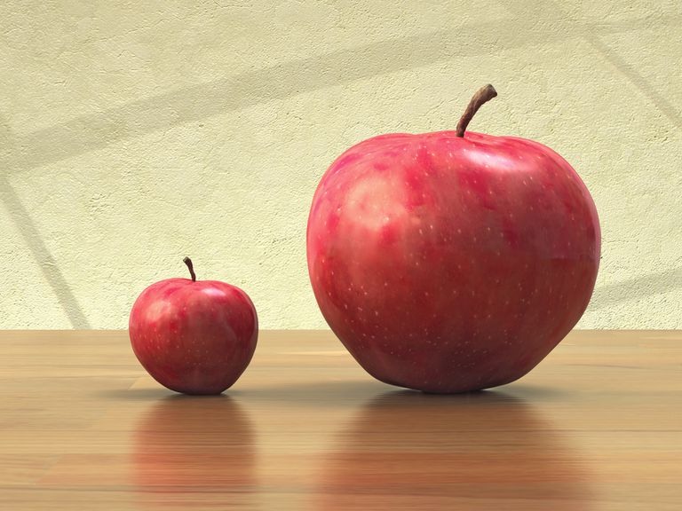 Two apples on a wooden tabletop, one big and one small