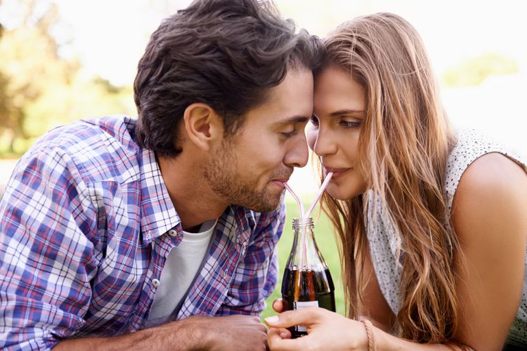 Couple drinking from the same soda bottle