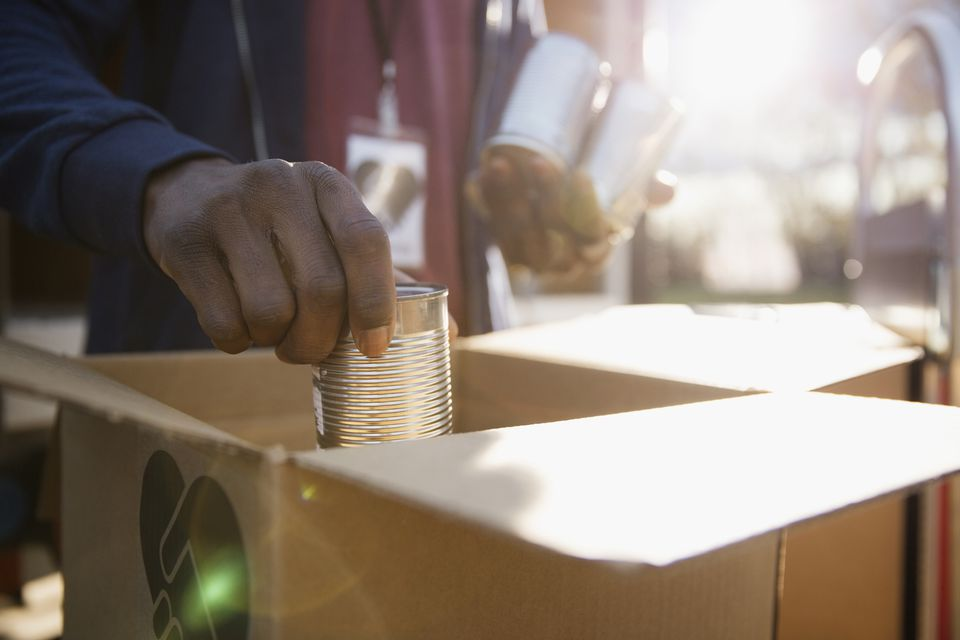 Man putting donated food cans into a box.