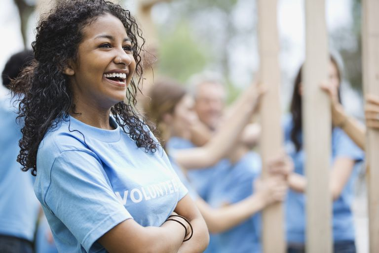 Cheerful teenage girl with volunteers building wooden frame in background