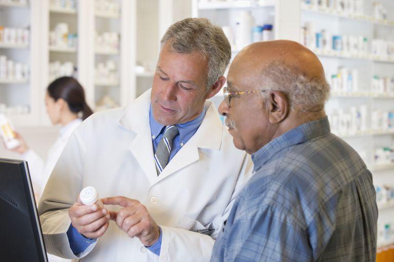 Elderly man talking with his pharmacist.