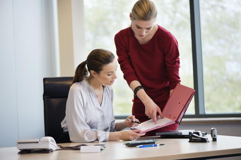 Businesswoman signing documents with her secretary