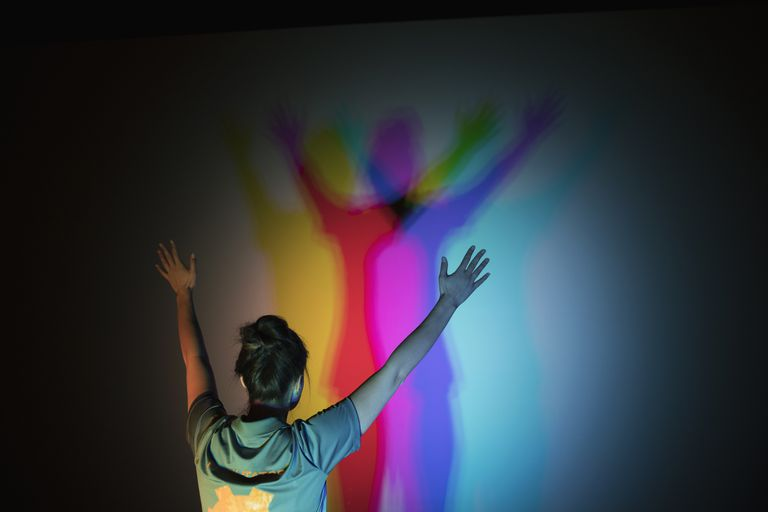Woman casting multicolor shadows on projection screen in science center theater