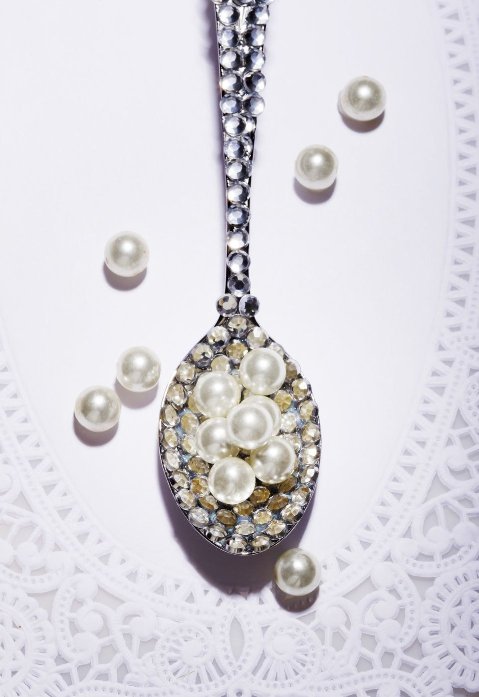 Diamond covered spoon full of pearls
